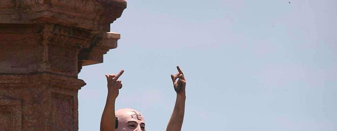Con una máscara del ex presidente Carlos Salinas de Gortari este manifestante se subió a una estatua para llamar la atención.