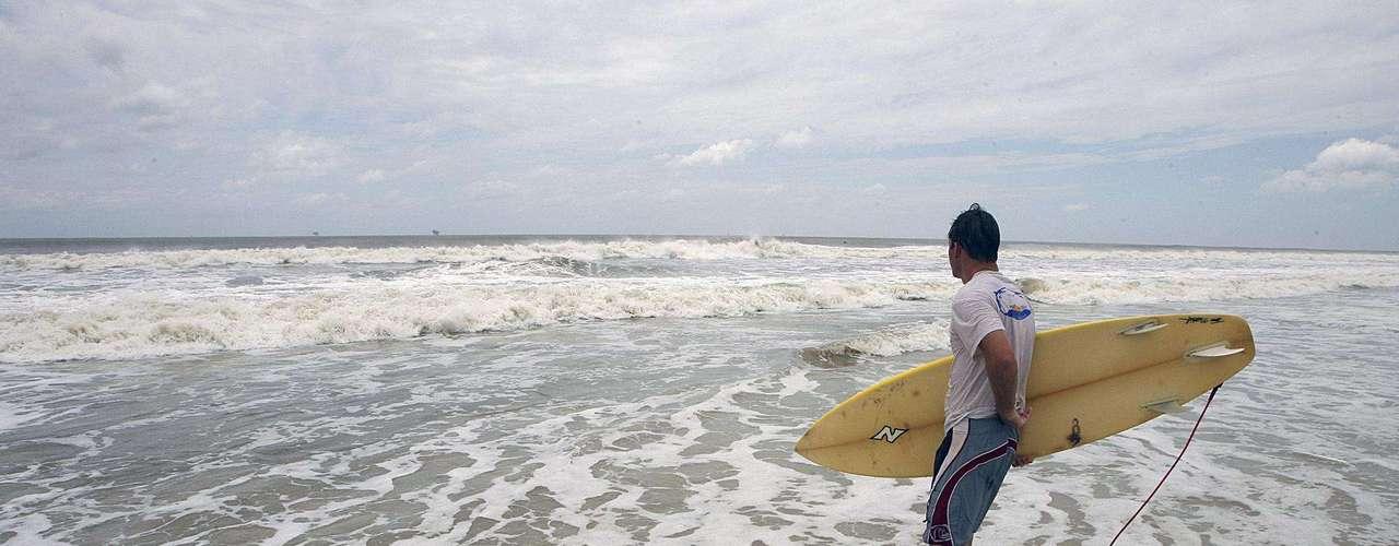 Un surfista se dirige al mar para aprovechar las olas en Dauphin Island, Alabama, debido a la agitación del mar con la tormenta tropical Debby, el domingo 24 de junio de 2012. (Foto AP/Mobile Register, Mike Kittrell)