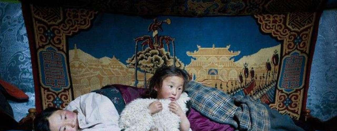 Erdene Tuya junto a su hijo Tuvchinj, 3 años. Tuvchinj, quien abraza un cordero que duerme con ellos, acaba de despertarse. Su marido, Batgargal, ha salido a echar un vistazo al rebaño acompañado de su otro hijo, Azjargal, de 6 años.