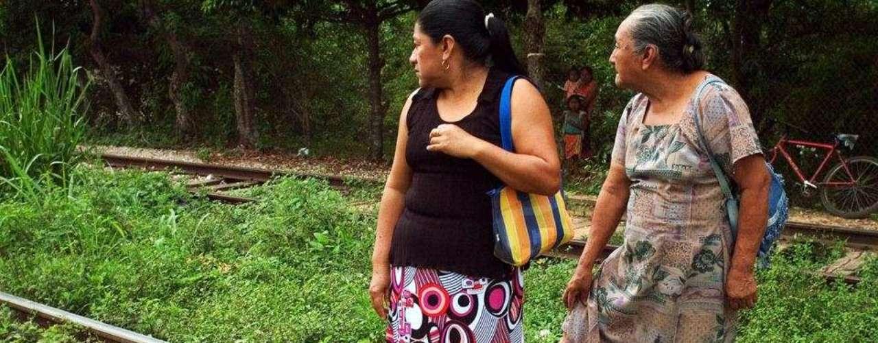 Estas dos mujeres esperan en las vías de tren de la Estación Chontalpa, Tabasco, para ofrecerles ayuda a los migrantes que cruzan México en su viaje hacia Estados Unidos. Los migrantes que viajan colgados de los vagones de los trenes encuentran cierto sosiego en la ayuda de estos pobladores locales que les dan comida gratis y en ocasiones les brindan espacio en sus hogares durante la peligrosa travesía. (Textos: BBC Mundo)