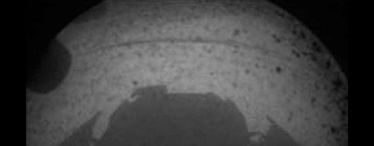 Las primeras imágenes enviadas por Curiosity son como ésta, en blanco y negro. En esta foto de gran angular es posible ver incluso la sombra del robot.