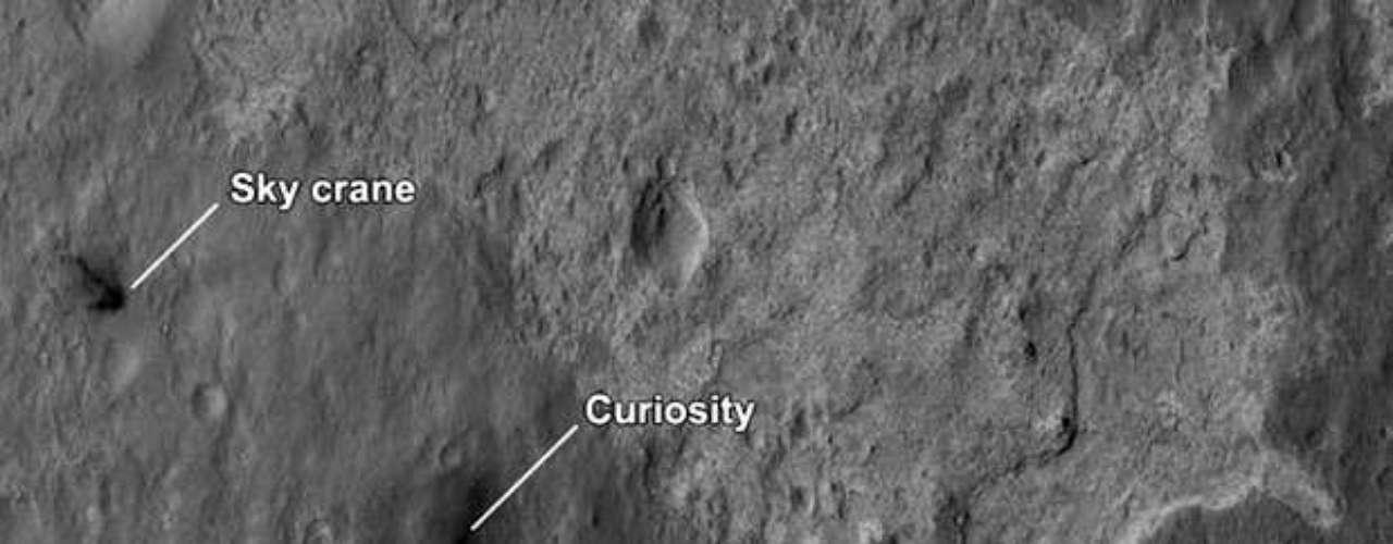 Una tercera imagen parcialmente panorámica en blanco y negro del norte del cráter muestra una extensa planicie cubierta de sedimentos con montañas más bien bajas a lo lejos.