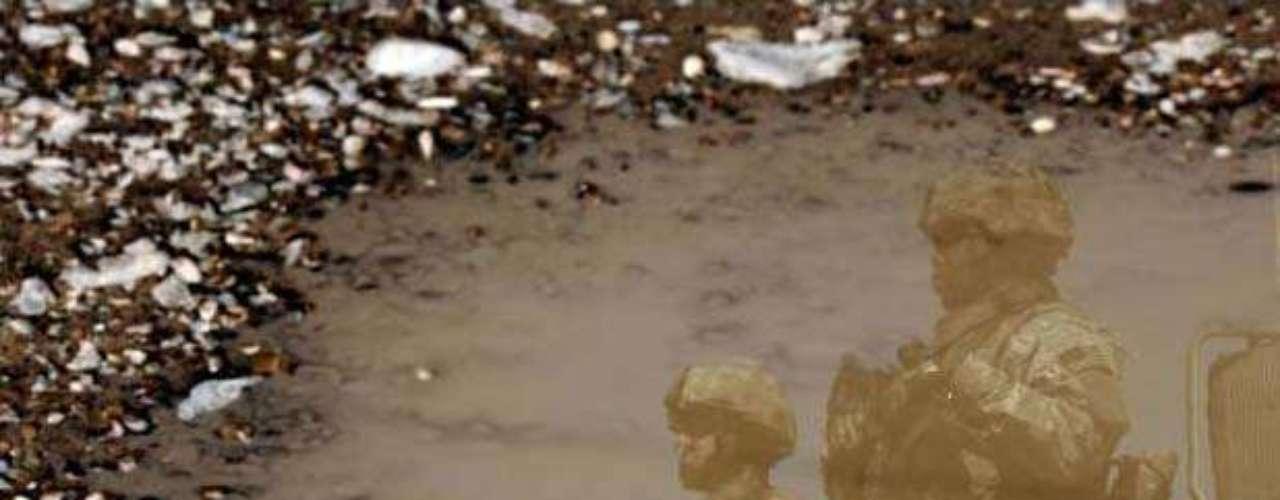 Pasé en Afganistán, más de un año. Al principio, estaba buscando mi camino. El coronel y el sargento mayor Kornish Andy me pusieron en contacto con la Infantería de Marina estadounidense en 2008. Nos adentramos en territorio talibán en la provincia de Helmand para seguir la operación Garmsir. Había un montón de oportunidades para hacer buenas fotos. En la foto, unos soldados estadounidenses se ven reflejados en un charco de agua, guardan sus vehículos frente a una comisaría de policía afgana en Kandahar, 16 de octubre 2007.