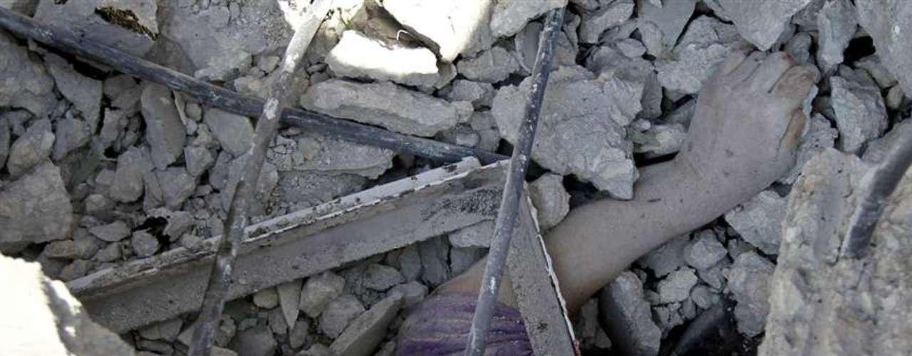El brazo de una mujer siria muerta a causa de los bombardeos sobre Asaz sobresale entre los cascotes de su casa. Gran parte de las víctimas del bombardeo son mujeres y niños que se encontraban en el interior de sus domicilios.