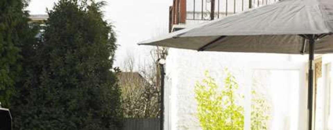 Patio con deck de madera: el detalle que distingue a este espacio está en la parrilla ubicada en el medio, sobre un cuadrado de piedras.