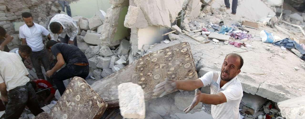 Un hombre ayuda a retirar los cascotes de un edificio derrumbado buscando supervivientes del bombardeo. Asaz es una ciudad de unos 70.000 habitantes y está considerada un bastión de los rebeldes.