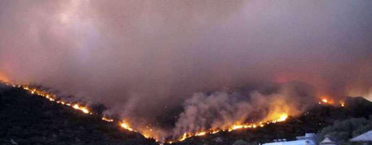 Ciudadanos de la localidad de Lithi se refugian en la playa mientras las llamas arrasan el monte frente a ellos en la isla de Chios, Grecia.