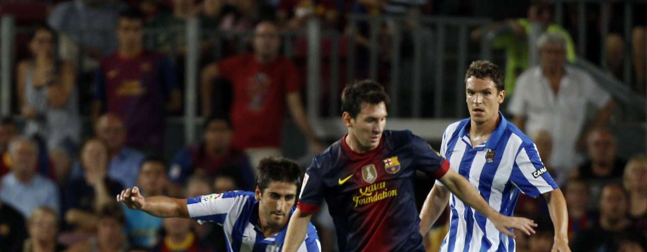 Lionel Messi controls the ball against Real Sociedad players. He scored two goals.