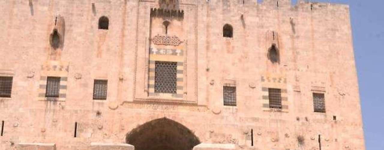 Soldados del ejército nacional sirio posan con la bandera oficial del régimen de Al Asad frente a la puerta interior del castillo de Alepo. El castillo es una de las siete ubicaciones reconocidas por la UNESCO como Patrimonio Histórico de la Humanidad en Siria.