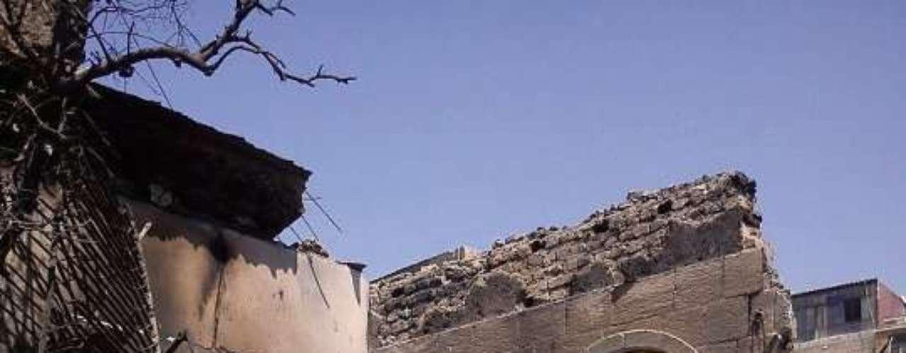 Una mujer mira a la cámara del fotográfo en el zoco destruido por un bombardeo, en el casco antiguo de Damasco. El mayor temor de los arquólogos radica ahora en la posibilidad de que la guerra se enquiste y dure años, imposibilitando el trabajo de recuperación de los yacimientos y museos dañados.