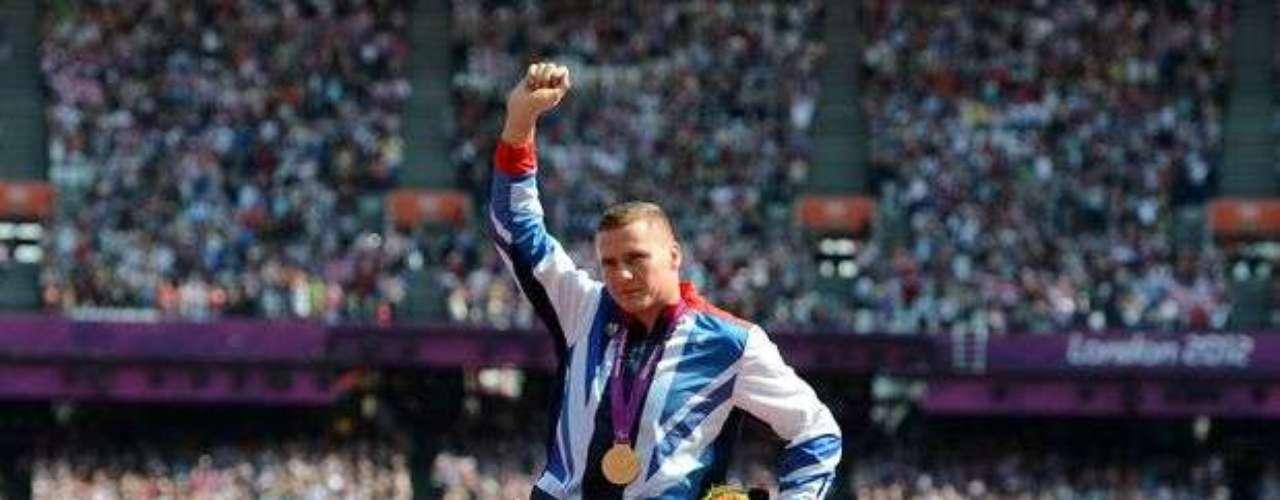 Defendiendo los colores de la anfitriona Gran Bretaña, David Weir es aplaudido al subir al podio y festeja la conquista de la medalla de oro en la final de los 5000 m T54, en silla de ruedas.