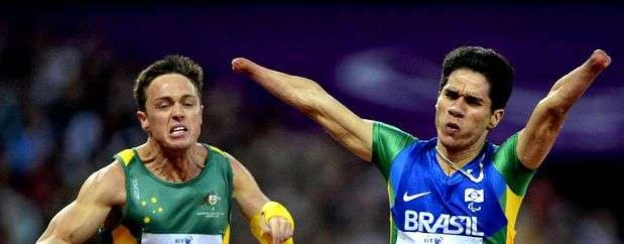 El brasileño Yohansson levanta los brazos durante la final del relevo, en disputa directa con un atleta sudafricano.