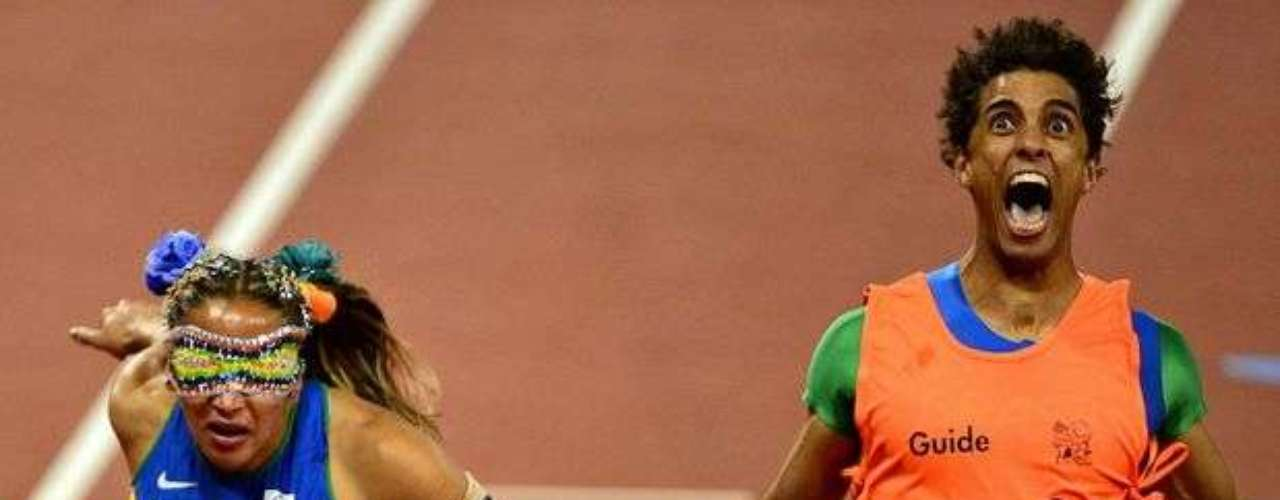 La brasileña Terezinha Guilhermina termina la prueba de los 100 m T11 en primer lugar. El guía de la ganadora, Guilherme Santana, que se había lesionado en una prueba, grita de alegría al final de la carrera.