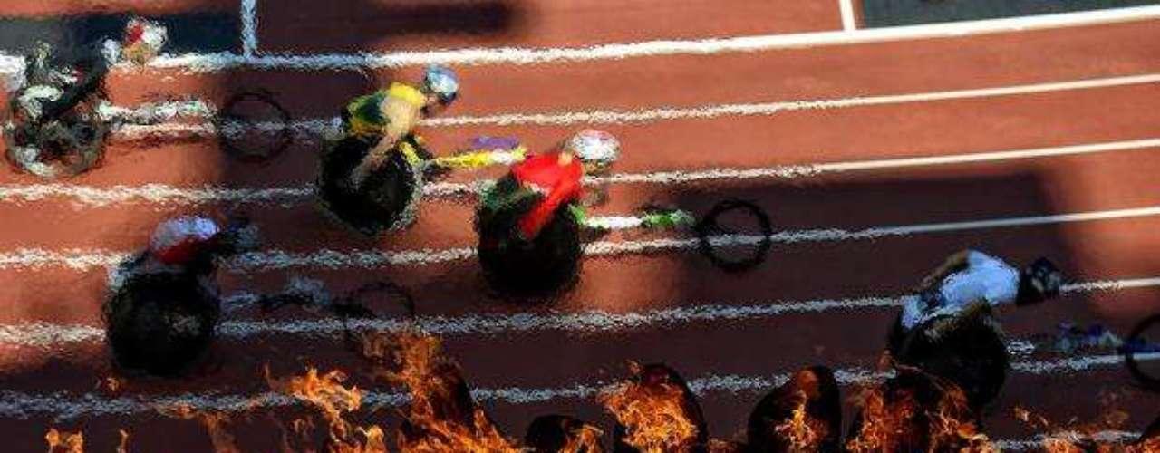El pebetero paralímpico ilumina el estadio durante una competición en silla de ruedas adaptadas.