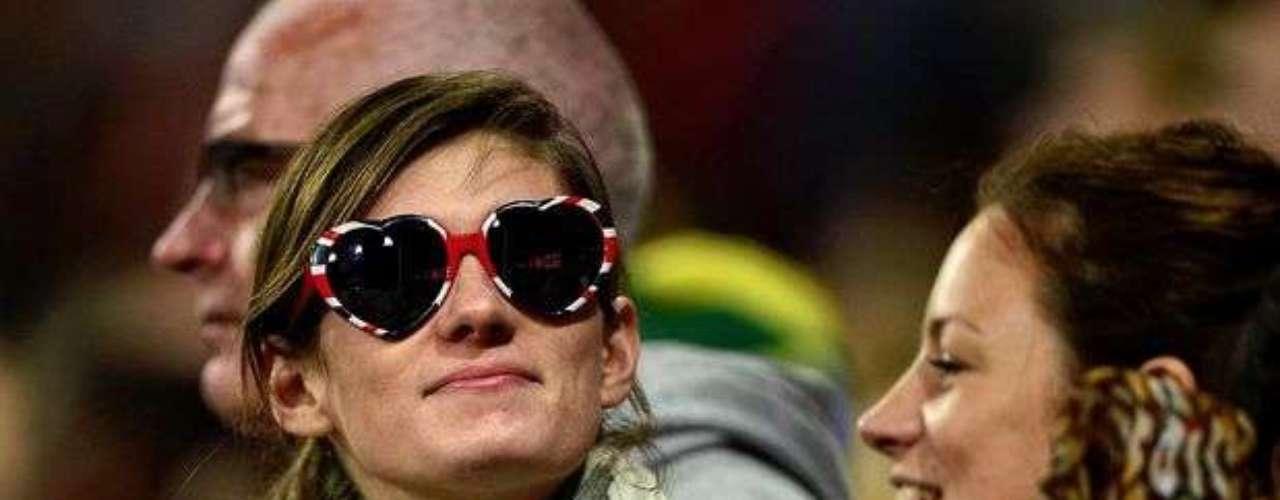 Las mujeres no dejan de estar a la moda a la hora de asistir a las pruebas de atletismo. En la imagen, una espectadora observa las pruebas usando anteojos en forma de corazón y con los colores de la bandera británica.