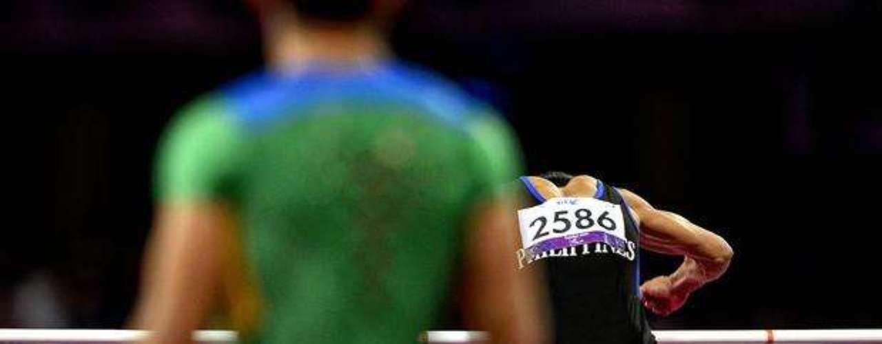 Los deportistas hacen un calentamiento previo a la competición de salto de altura.