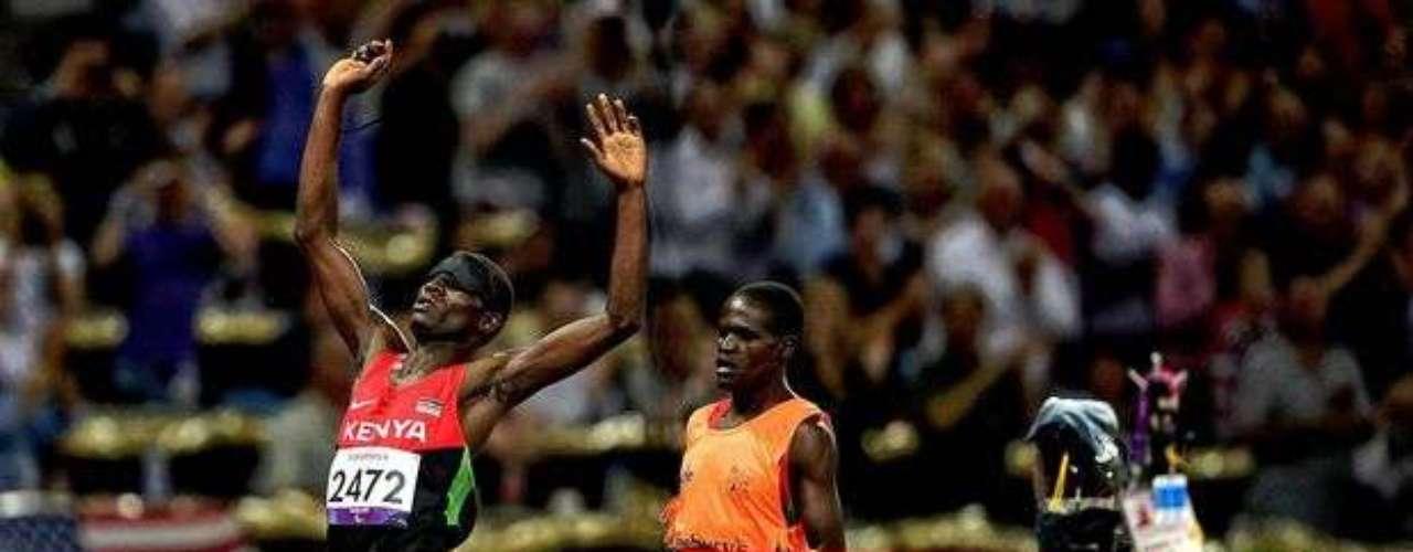 Este atleta keniano festeja el resultado de la prueba mientras el marcador electrónico muestra la superación del récord mundial.