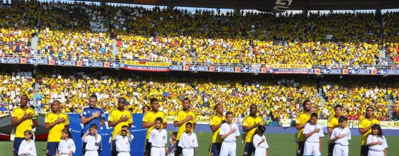 Los jugadores del onceno colombiano con las manos derechas en sus pechos, para el himno nacional.