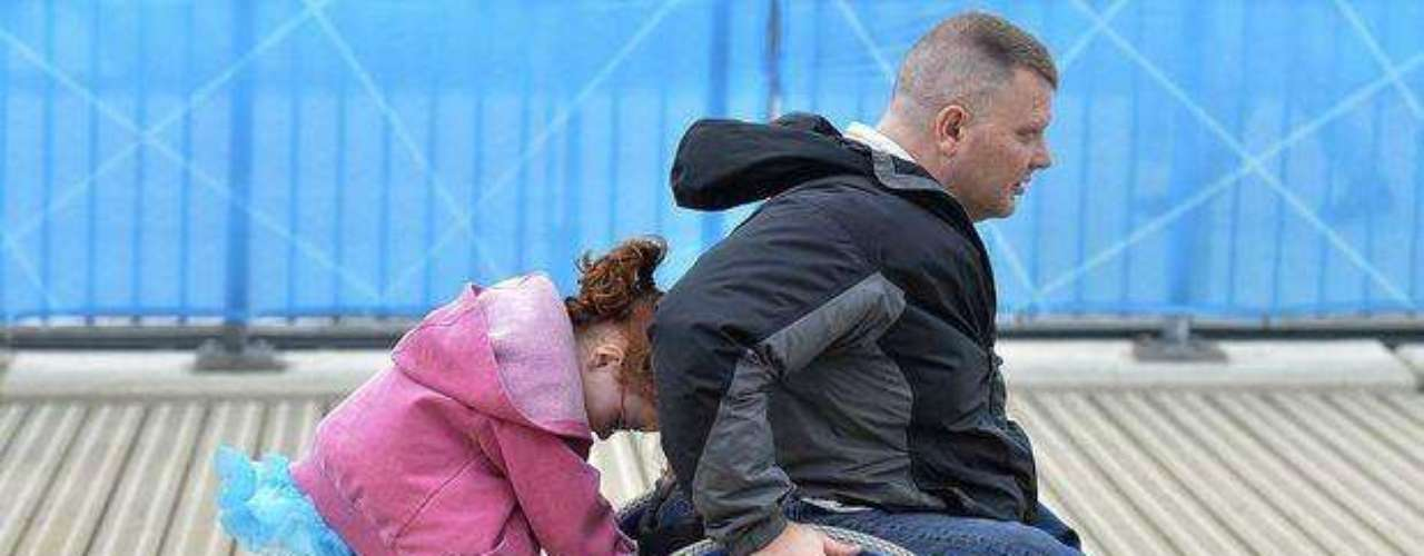 Una niña emociona al Parque Olímpico al bajar de los brazos de su padre, que anda en silla de ruedas, para empujarlo y ayudarlo a subir una rampa.