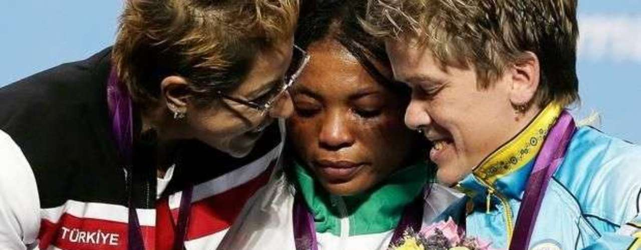 Emocionados, Ivory Nwokorie, de Nigeria; Cigdem Dede, de Turquía; y Lidiia Soloviova, de Ucrania, se abrazan en el podio femenino del levantamiento de peso de hasta 44 kg.