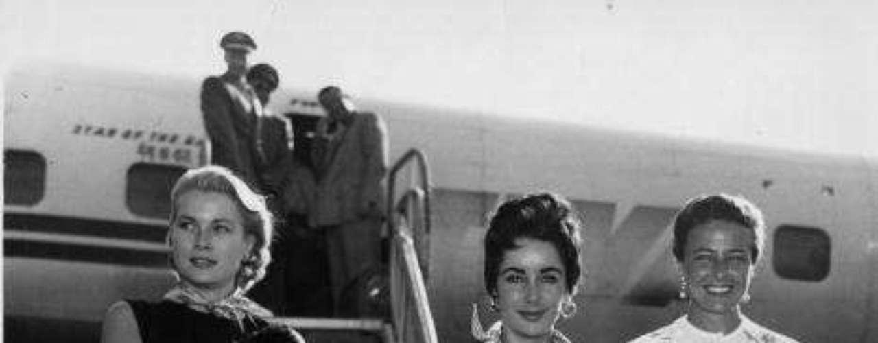 En esta fotografía tomada en 1955, Grace Kelly posa junto a Elizabeth Taylor y Lorraine Day a su llegada al aeropuerto de Nueva York.