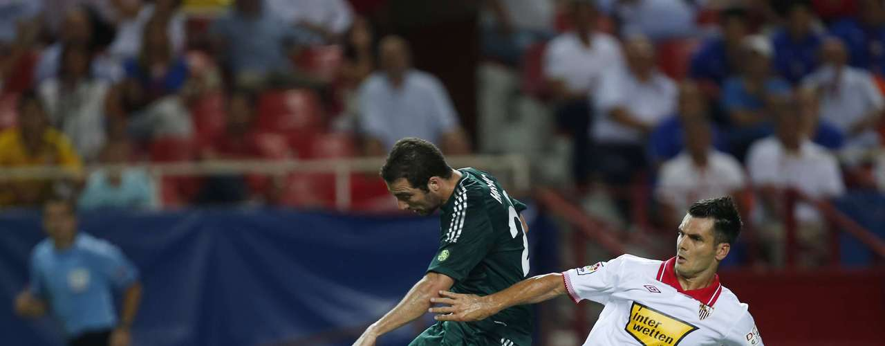 Real Madrid's Gonzalo Higuain (L) is challenged by Sevilla's Emir Spahic during their Spanish First Division soccer match at Ramon Sanchez Pizjuan stadium in Seville September 15, 2012. REUTERS/Marcelo del Pozo (SPAIN - Tags: SPORT SOCCER)