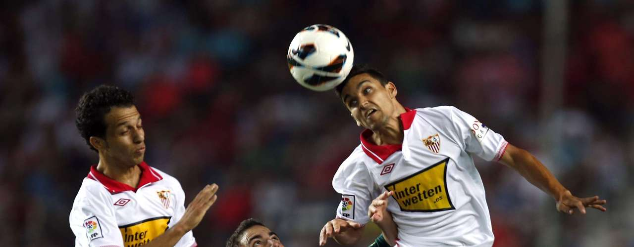 Sevilla's Jesus Navas (R) heads the ball next to Alex Sandro Mendoza Cicinho (L) and Real Madrid's Gonzalo Higuain during their Spanish First Division soccer match at Ramon Sanchez Pizjuan stadium in Seville September 15, 2012. REUTERS/Marcelo del Pozo (SPAIN - Tags: SPORT SOCCER)