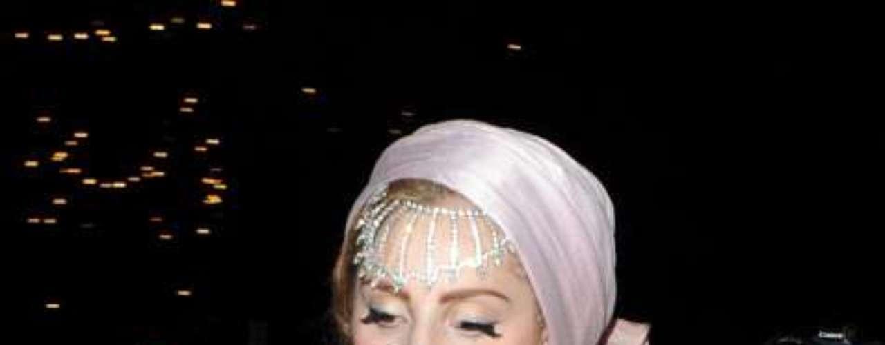 Gaga acaparó todas las miradas en la primera jornada de la Semana de la Moda de Londres. La cantante, gracias a sus excéntricos looks, dejó en segundo plano a los diseñadores de la pasarela londinense. Gaga desfiló para el diseñador Philip Treacy con una capa rosa flúor que cubría todo su cuerpo. Al ser semitransparente, se pudo ver que debajo llevaba puesto un ajustado mono color carne flores estampadas. Minutos antes del desfile, la cantante lució un vestido de terciopelo verde y leggins doradas. Pero todas las miradas se desviaban a su cabeza, en la que llevaba una corona de flores que le cubría toda la cara. También se la vio con unas enormes orejas de Minnie Mouse con incrustaciones de pedrería que hacían juego con su camisa, encima de la que llevaba una chaqueta blanca decorada con perlas. Esto no fue todo, Lady Gaga sorprendió al público londinense con un último cambio de vestuario: un modelo turbante que incluía pieles colgantes.