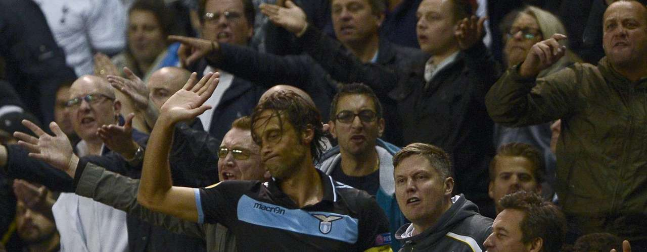 A fan pulls the arm of Lazio player Stefano Mauri