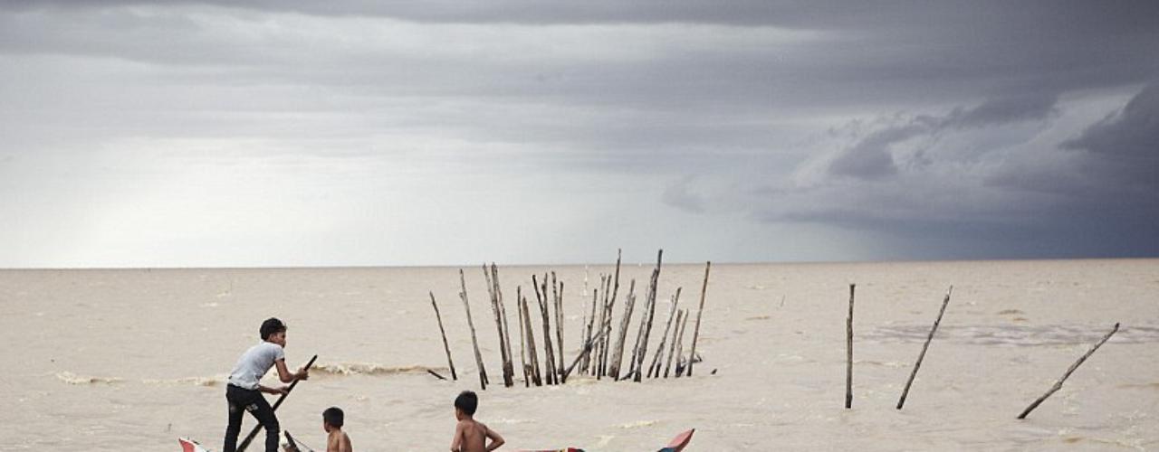 Estos niños intentan escapar a una tormenta en Cambodia. Fotografía de  Zachary Bako.