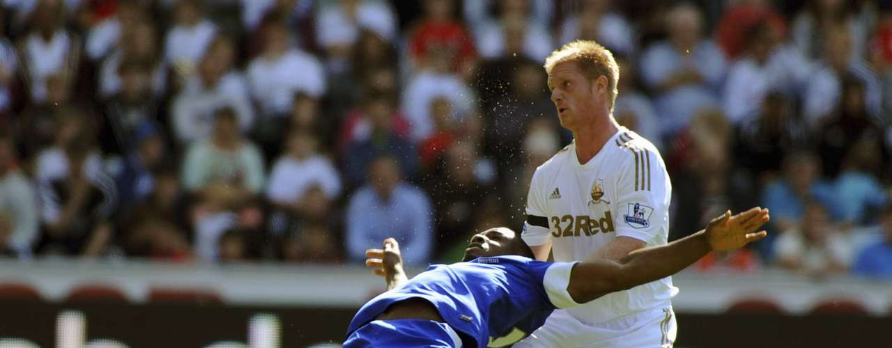 Swansea's Alan Tate (R) challenges Everton's Victor Anichebe.