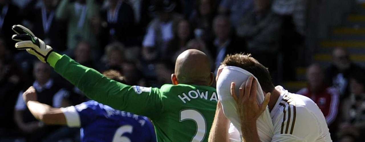 Swansea City's Angel Rangel (R) holds his head in his shirt after an attempt on goal goes wide.