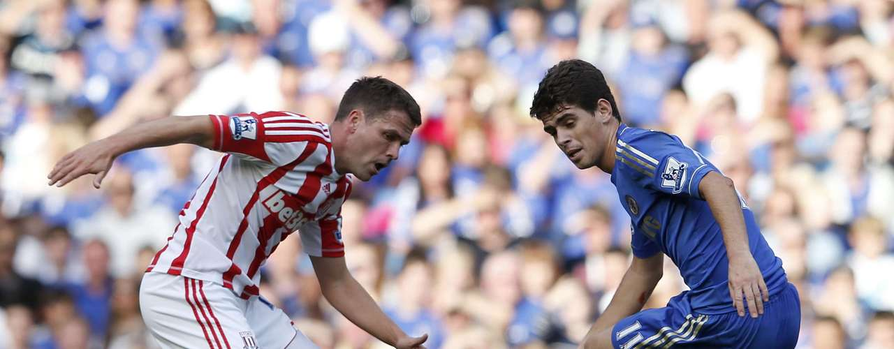 Chelsea's Oscar (R) is challenged by Stoke City's Michael Owen.