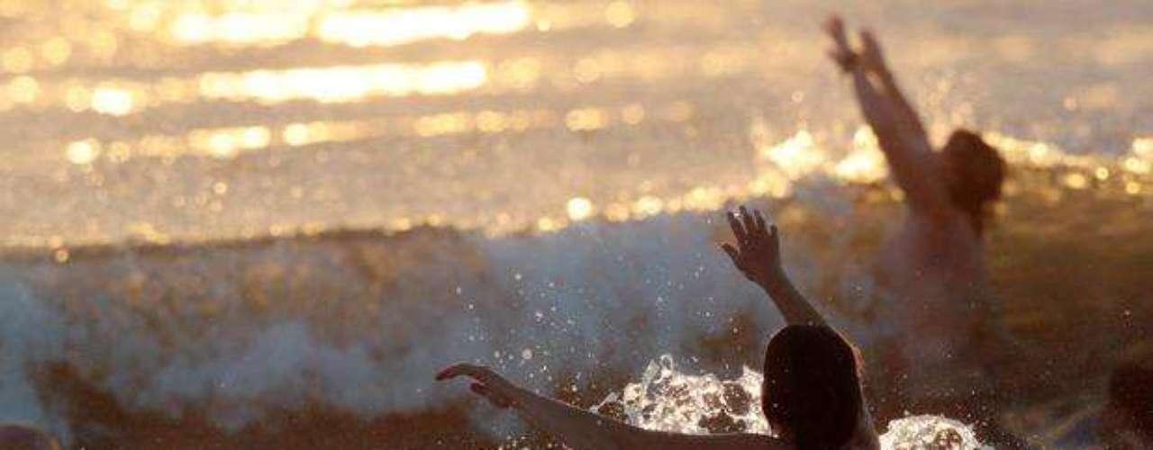 Una joven lucha contra una ola, durante el intento de cientos de nudistas por conseguir el récord mundial del chapuzón de nudistas más multitudinario del mundo. Su esfuerzo fue en vano.