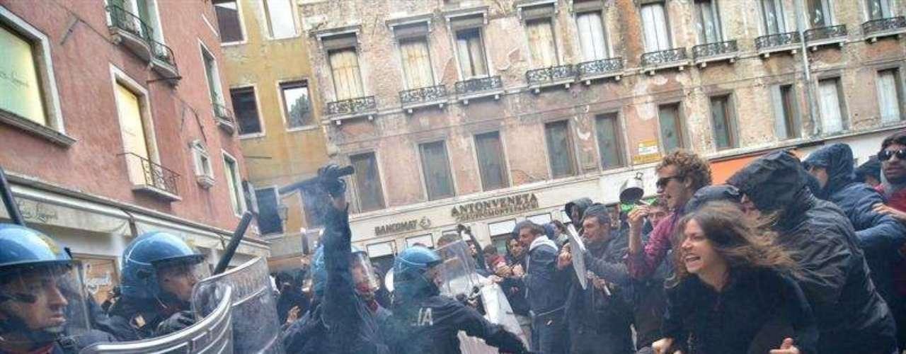 Jóvenes italianos se enfrentan a miembros de la Policía durante la protesta en Venecia.
