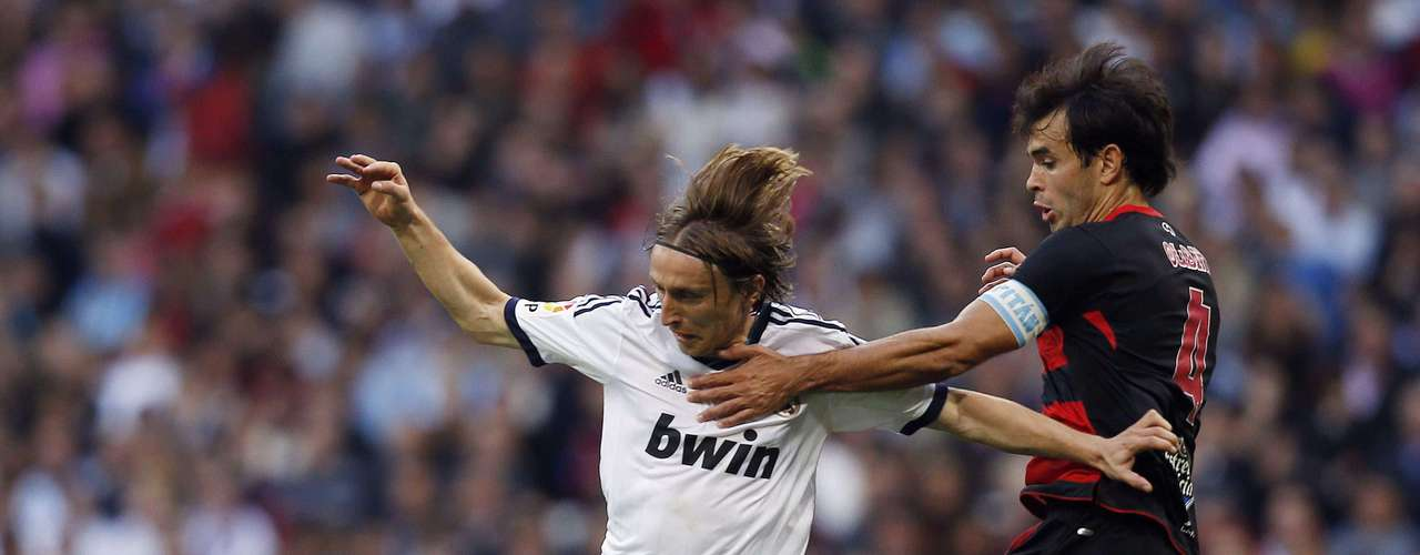 Real Madrid's Luka Modric (L) fights for the ball with Celta Vigo's Borja Oubina during their Spanish First Division soccer match at Santiago Bernabeu stadium in Madrid October 20, 2012. REUTERS/Susana Vera (SPAIN - Tags: SPORT SOCCER)