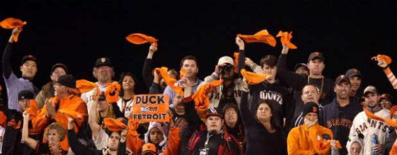 La afición de Giants apoyan a su equipo agitando sus toallas anaranjadas.