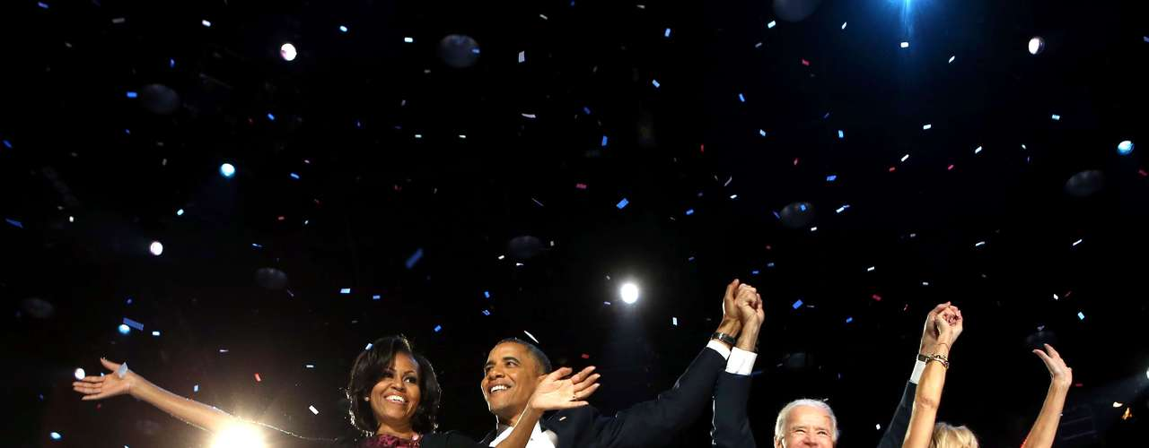 The Obama and Biden families raise their arms in celebration Tuesday night in Chicago, Illinois.