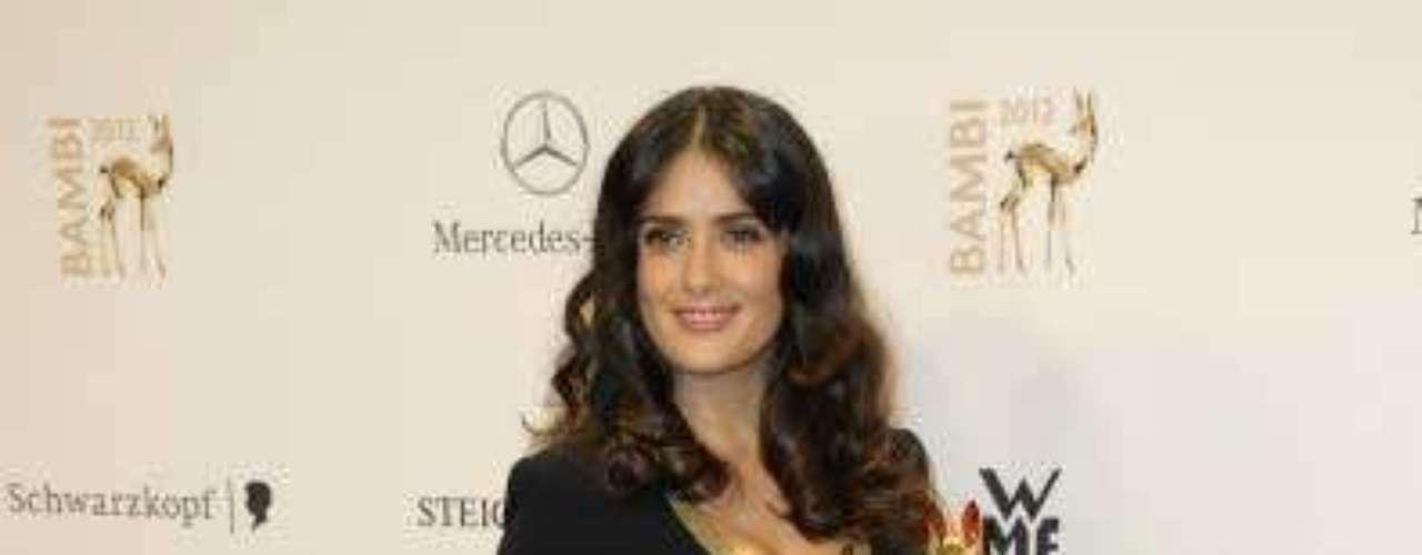 La veracruzana Salma Hayek apareció enfundada en este sexi atuendo en negro con aplicaciones en dorado en puños y escote. Las prominentes curvas de la actriz hicieron que este simple atuendo tuviera un toque de gran sensualidad. El cabello lució poco arreglado.