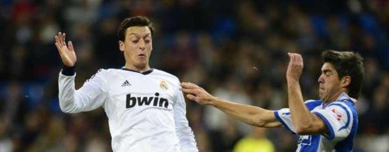 El jugador del Real Madrid, Mezut Özil, lucha por un balón con Devesa