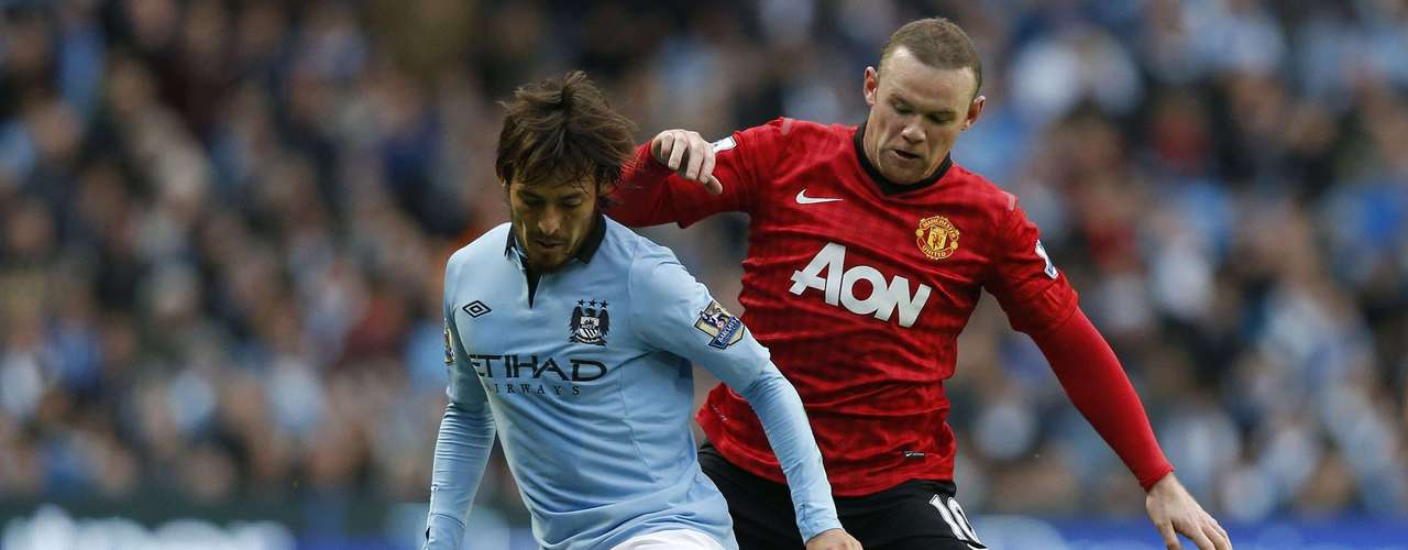 Manchester City's David Silva (L) challenges Manchester United's Wayne Rooney.