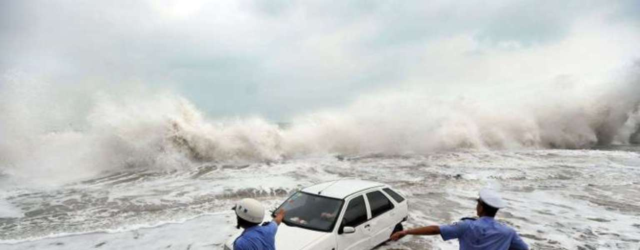 Policías ayudan al conductor de un vehículo a sacar su carro de la playa después de que las olas lo arrastraron, debido a la acción del tifón Bolaven en Qingdao, China.