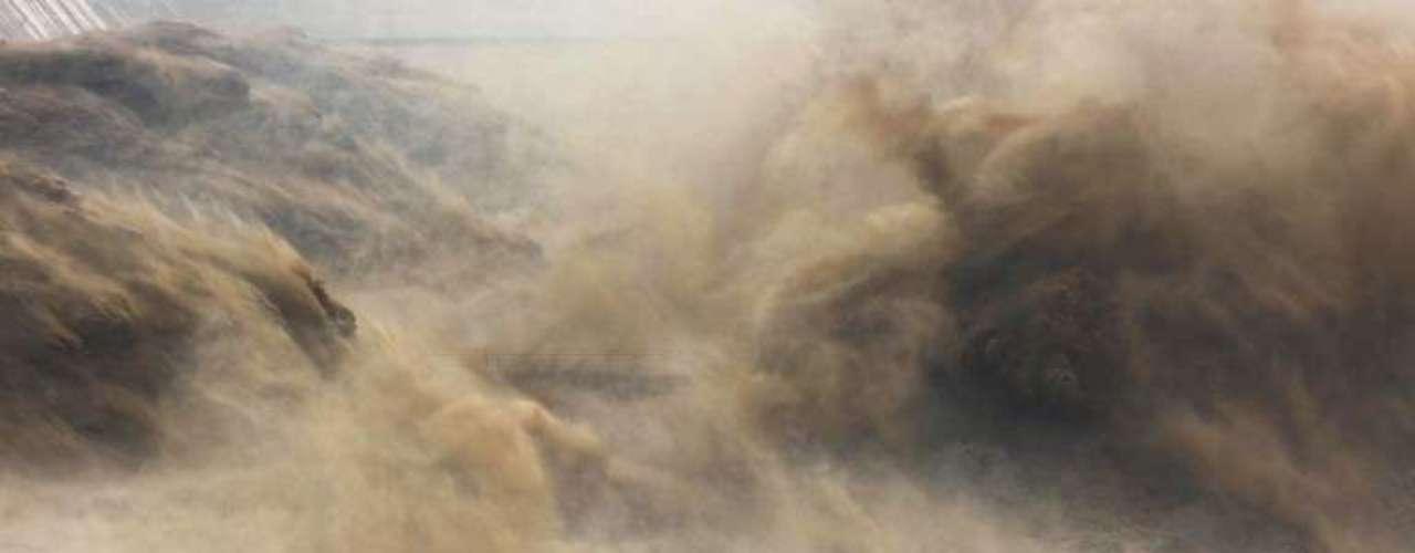 Visitantes observan la apertura de una represa en Río Amarillo (Huang He), en Jiyuan, China.
