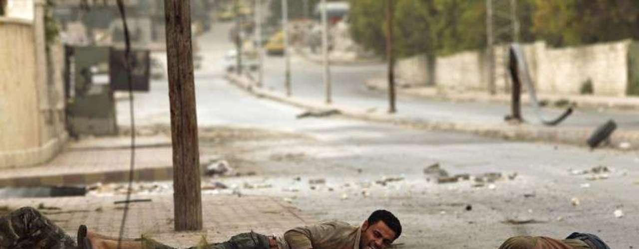 Rebeldes intentan arrastrar a un hombre herido por fuerzas del Ejército, en Aleppo, Siria.