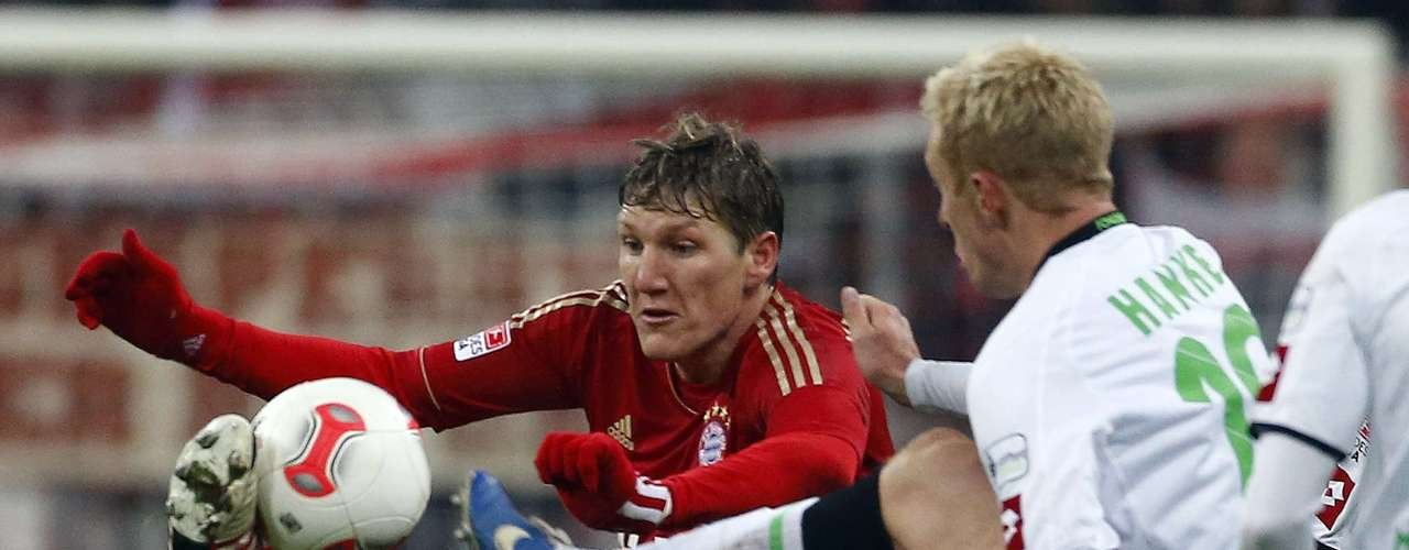 Bayern Munich's Bastian Schweinsteiger (L) fights for the ball with Hanke. REUTERS/Dominic Ebenbichler