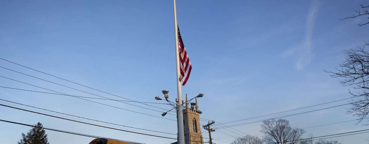 A flag is seen at half mast as a school bus passes along Main Street in Newtown, Connecticut December 14, 2012. A heavily armed gunman opened fire on school children and staff at a Connecticut elementary school on Friday, killing at least 26 people, including 18 children, in the latest in a series of shooting rampages that have tormented the United States this year. REUTERS/Shannon Stapleton (UNITED STATES - Tags: CRIME LAW EDUCATION TPX IMAGES OF THE DAY)
