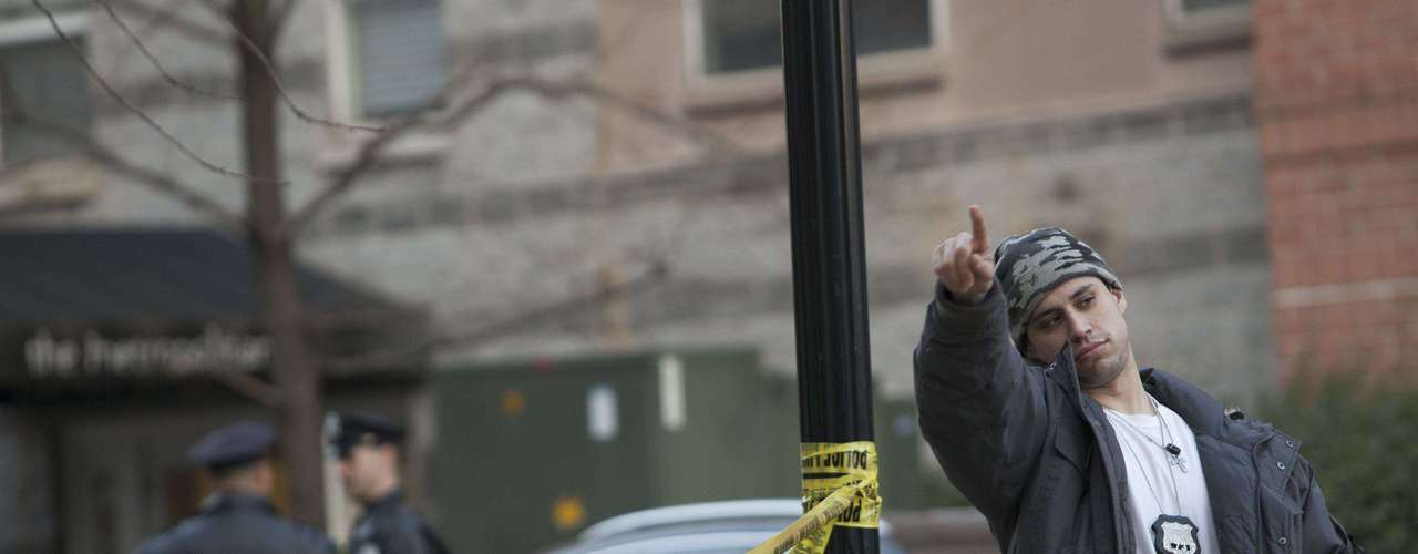 A plainclothes police officer gestures at a crime scene related to the shootings at Sandy Hook Elementary School, in Hoboken, New Jersey, December 14, 2012. In Hoboken, New Jersey, police cordoned off a block in connection with the Connecticut shootings but an officer told reporters there was no body inside, contrary to an earlier media report. REUTERS/Andrew Kelly (UNITED STATES - Tags: CRIME LAW EDUCATION)