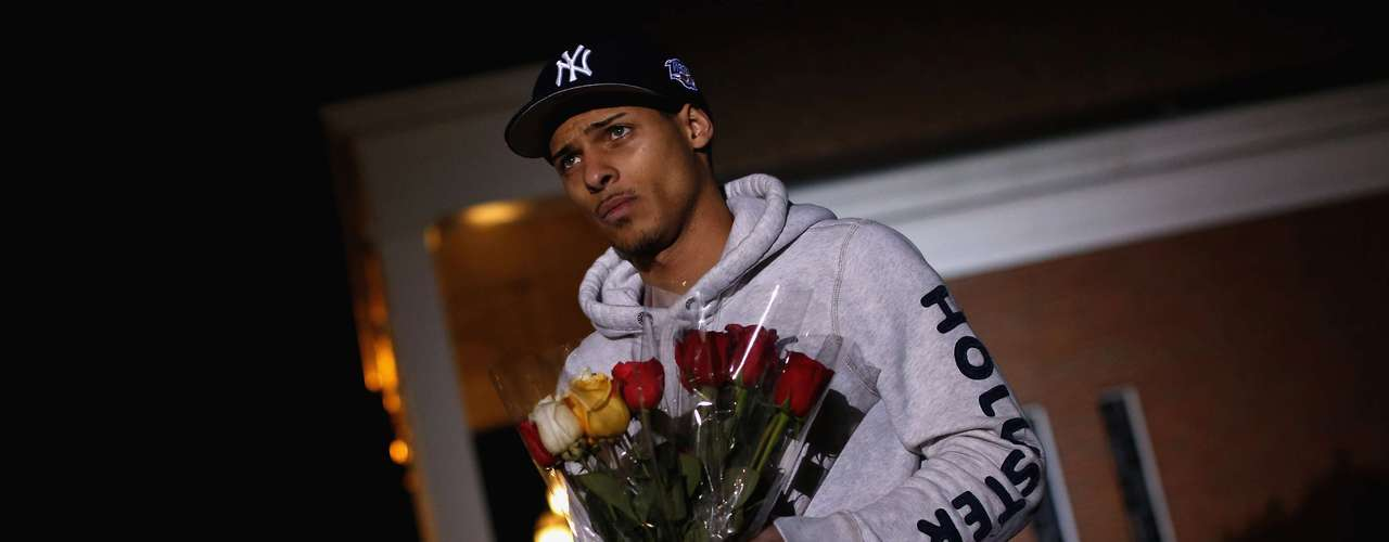 Anthony Baracey holds flowers honoring victims of the Sandy Hook Elementary school killing before a vigil at the Saint Rose of Lima church in Newtown, Connecticut December 14, 2012. A heavily armed gunman opened fire on school children and staff at a Connecticut elementary school on Friday, killing at least 26 people, including 20 children, in the latest in a series of shooting rampages that have tormented the United States this year. REUTERS/Shannon Stapleton (UNITED STATES - Tags: CRIME LAW EDUCATION)
