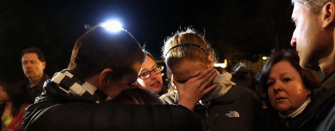 People grieve outside the overflow area of a vigil at the Saint Rose of Lima church in Newtown, Connecticut December 14, 2012. A heavily armed gunman opened fire on school children and staff at a Connecticut elementary school on Friday, killing at least 28 people, including 20 children, in the latest in a series of shooting rampages that have tormented the United States this year. REUTERS/Shannon Stapleton (UNITED STATES - Tags: CRIME LAW EDUCATION)