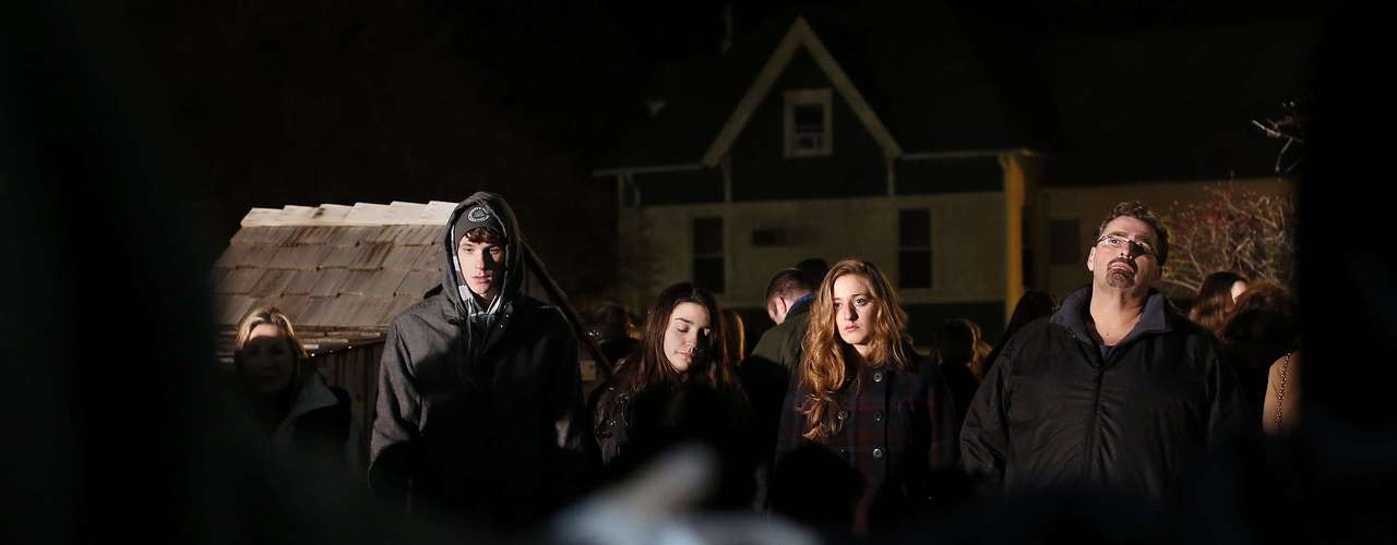 People stand in a prayer circle in the overflow area of a vigil at the Saint Rose of Lima church in Newtown, Connecticut December 14, 2012. The peace and security of the suburban Connecticut community of Newtown lay shattered on Friday after a gunman attacked a primary school in one of the worst mass shootings in U.S. history. Tearful parents and children gathered around Sandy Hook Elementary School by midday on Friday, surrounded by police vehicles, as young and old alike struggled to make sense of a shooting rampage that killed at least 28 people, including 20 children. REUTERS/Shannon Stapleton (UNITED STATES - Tags: CRIME LAW EDUCATION)